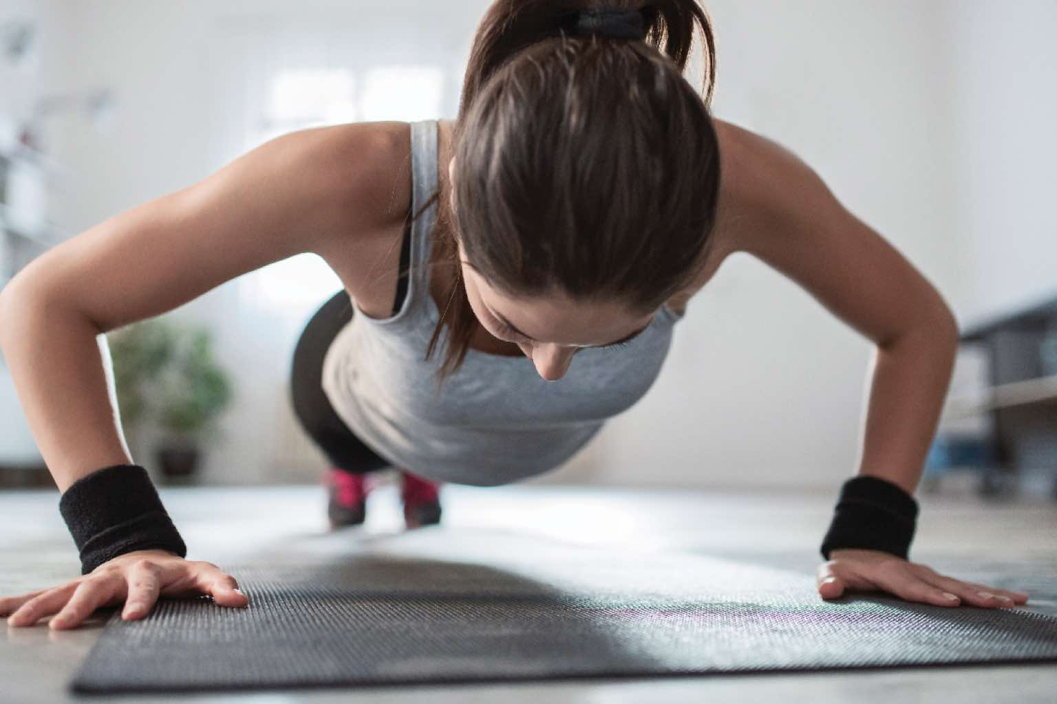 Woman doing push-ups on a yoga mat in a fitness studio at Life Time