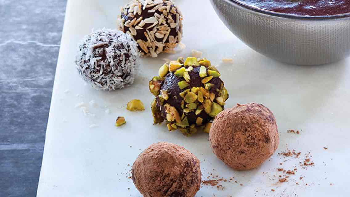 Five chocolate truffles with nut and coconut toppings set on a countertop