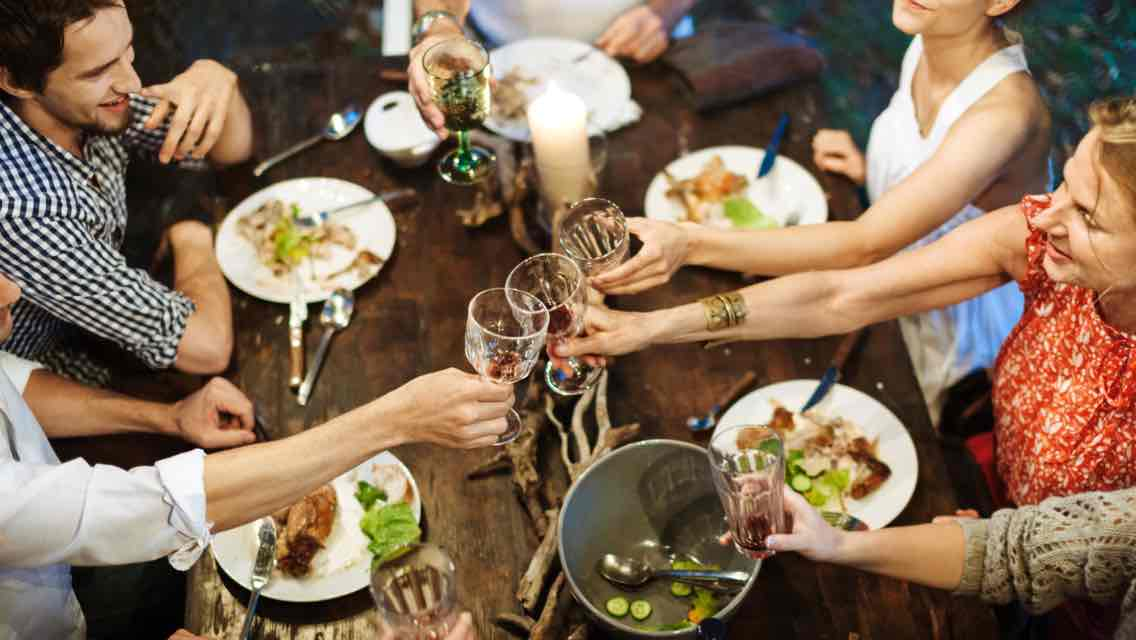 Aerial view of six people clinking their glasses together at a table with holiday food