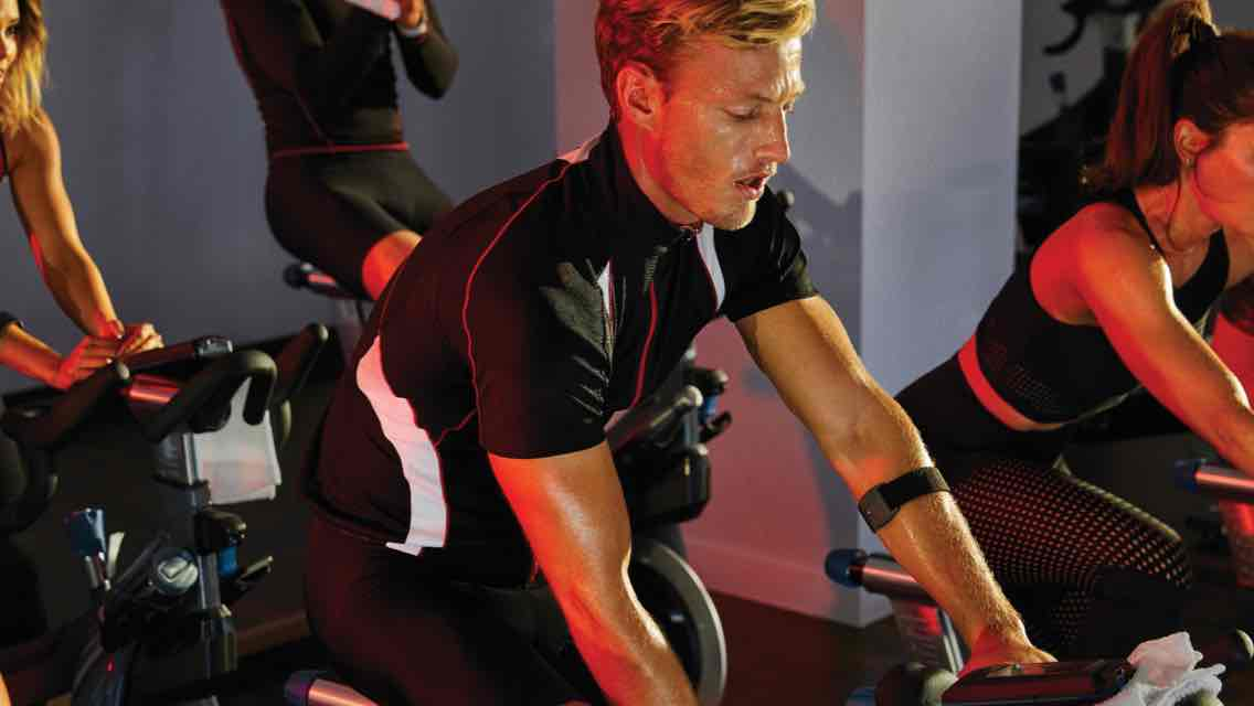 People participating in an indoor cycle class at Life Time