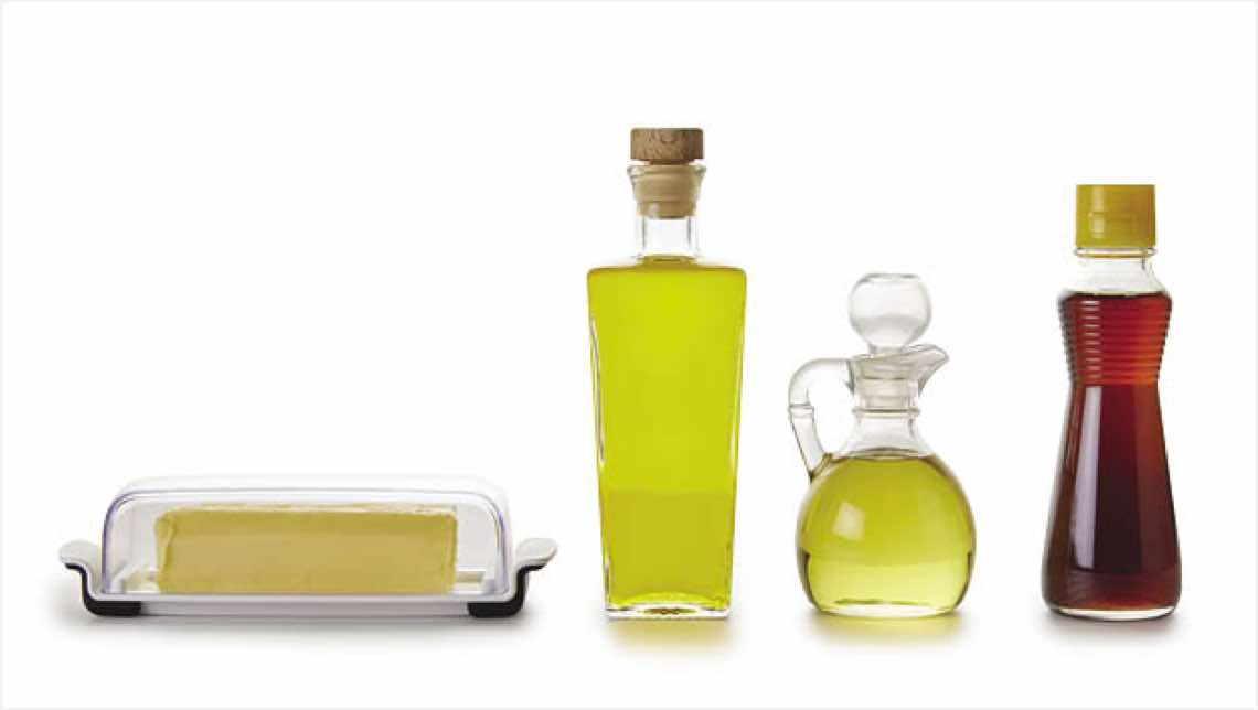 Stick of butter in a glass container and bottles of cooking oils