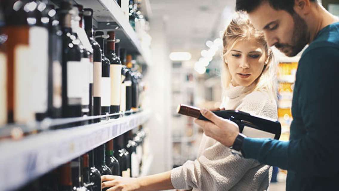 Man and woman looking at bottles of wine in a store