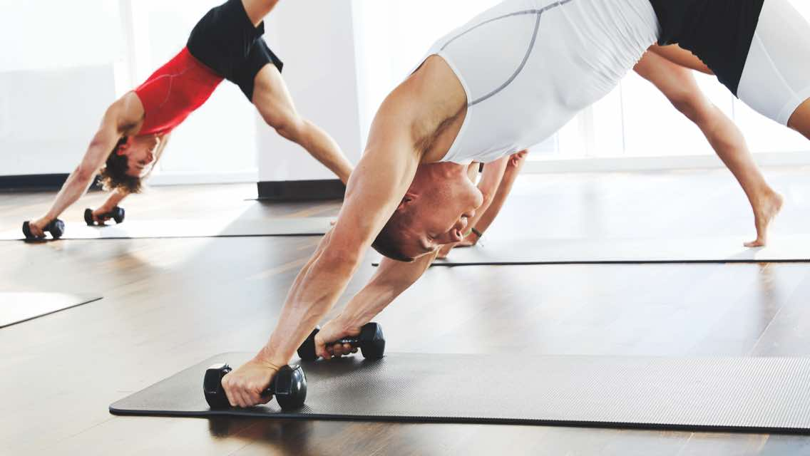Two men holding yoga poses on yoga mats at Life Time