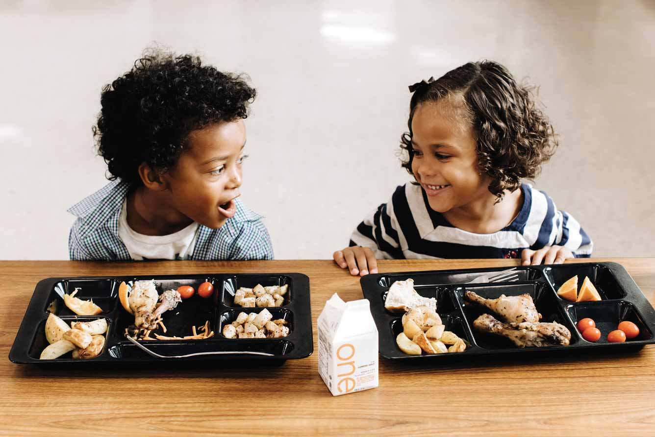 Two young children happily eating a healthy school lunch