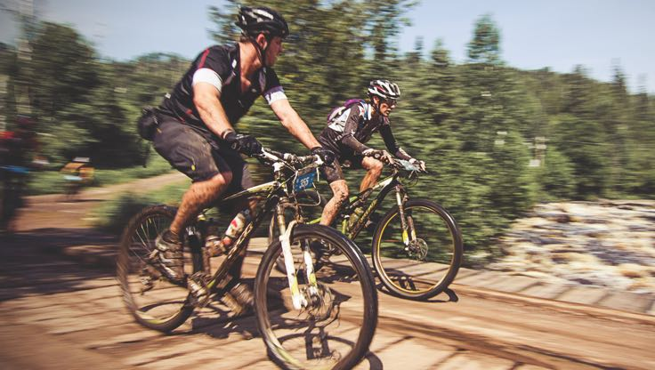 Two bikers in Life Time Cycle gear racing on a trail through a forested area