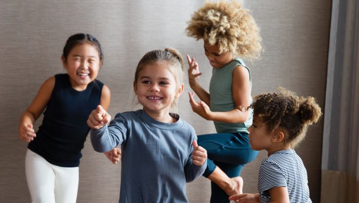 A group of young girls dance around together in a studio