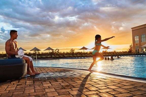 A father watches his daughter jump into the pool as the summer sun starts to set
