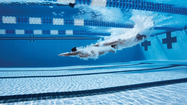 A person gliding through the pool water with their arms over their head