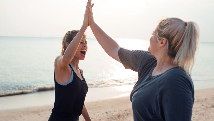 Two women in athletic clothing high five and smile at each other while standing near the water on a beach