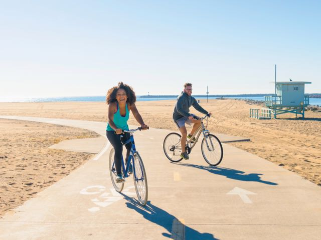 A man and woman smile happily while riding bikes on the beach