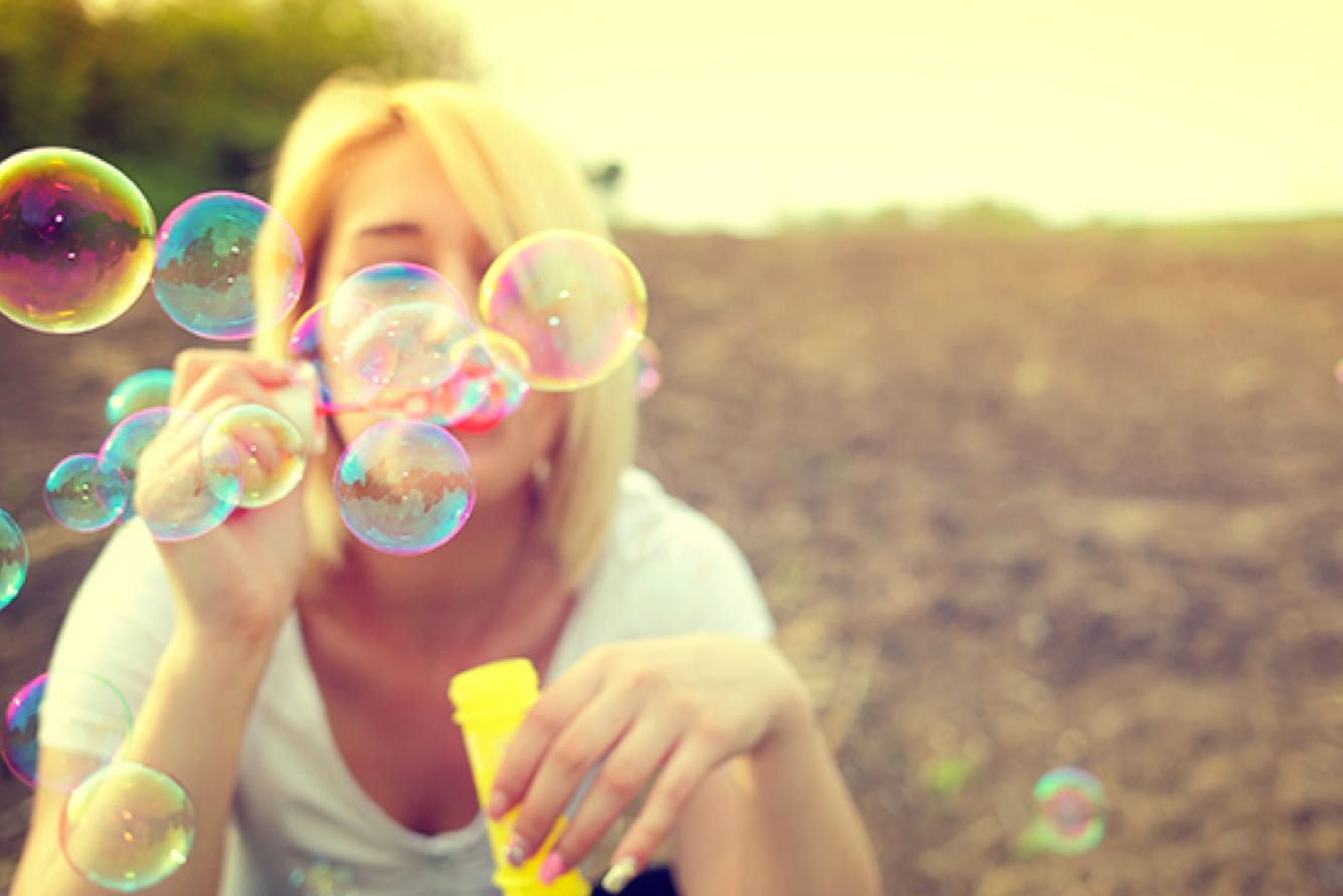 a women blowing bubbles towards the camera