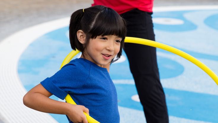 A girl in a blue T-shirt holds a yellow hula hoop in both hands and prepares to spin it around her waist