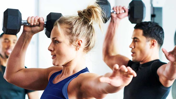 Two people hold dumbbells above their head in their right hands and hold their left hands straight out to their sides