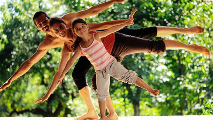 Three family members stand tallest to shortest and hold a triangle yoga pose with a background of leafy green trees