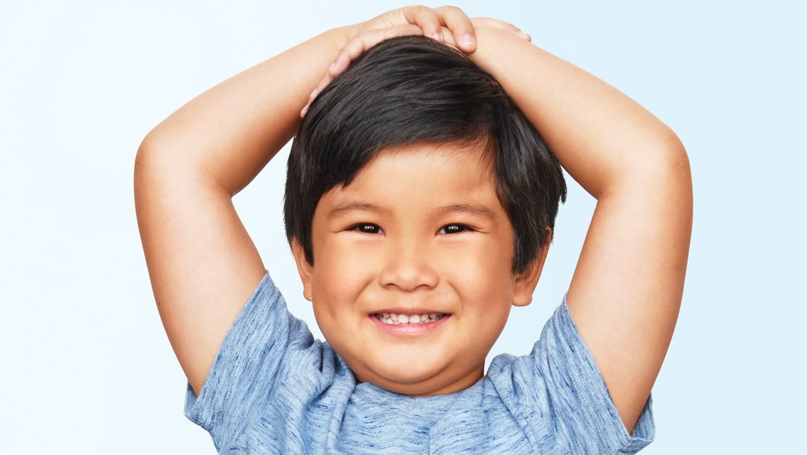 A male child smiles while holding his arms above his head with his hands placed on the top of his head