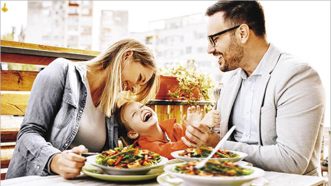 Two adults and a child sit and laugh together at an outdoor restaurant with three salads on their table