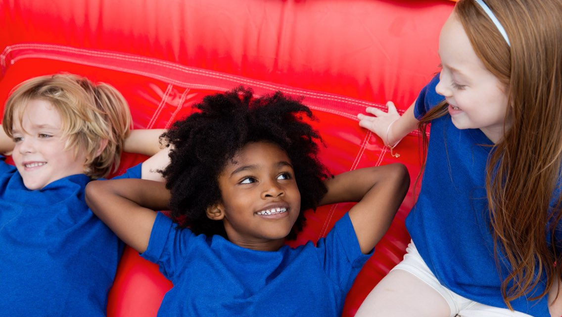 Three kids wearing blue shirts sit together on a red play mat