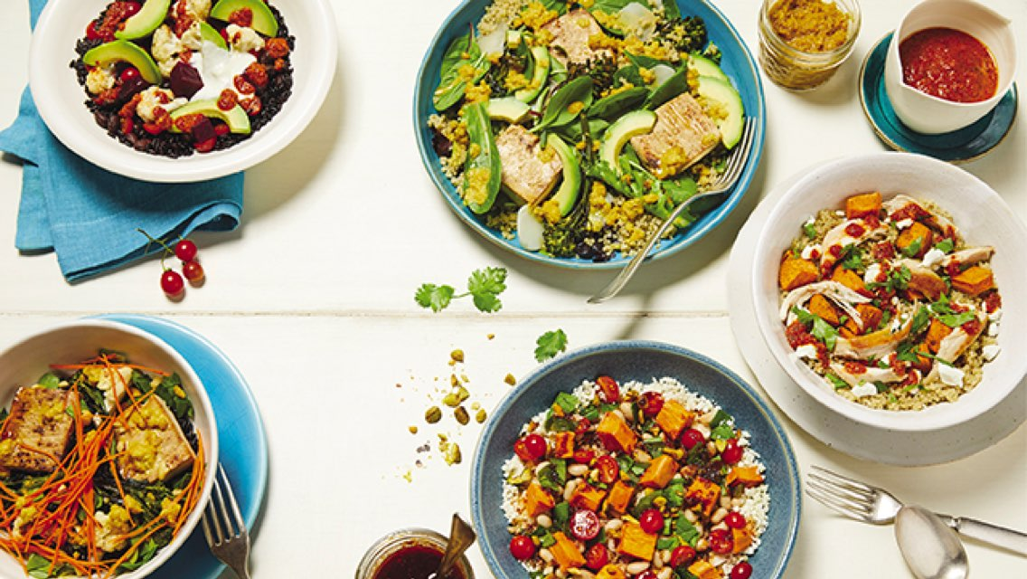 A table spread of salads and grain bowls with fresh ingredients with assorted silverware