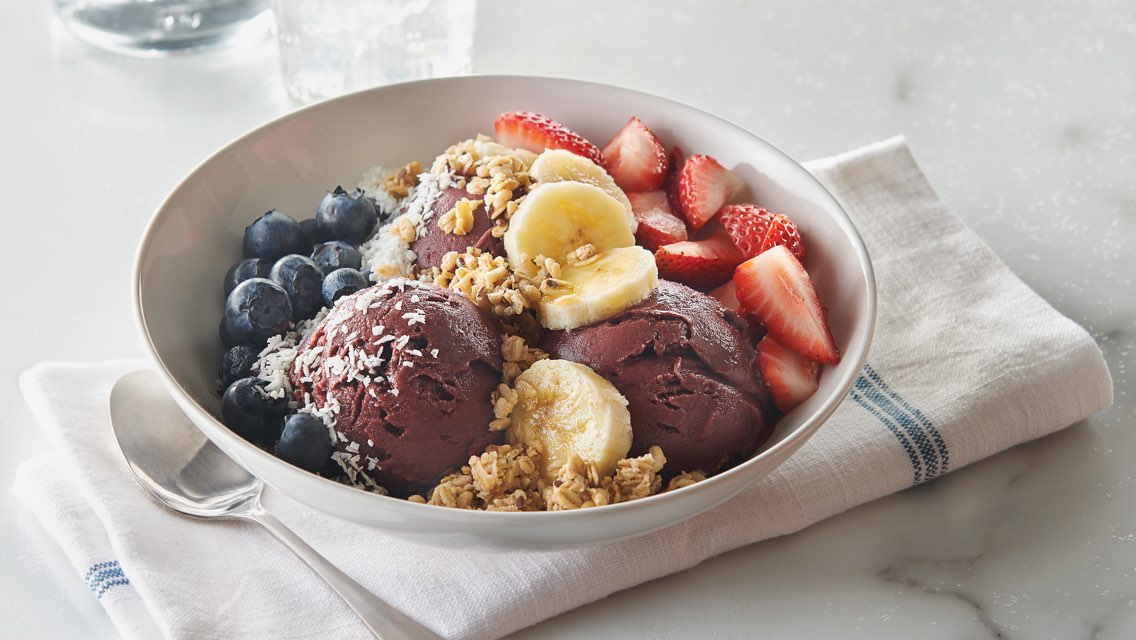 A LifeCafe power bowl with acai, blueberries, chopped strawberries and banana topped with coconut flakes and granola