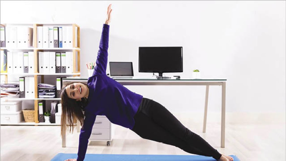 A woman in a side plank position on a blue yoga mat with a book shelf and computer desk in the background