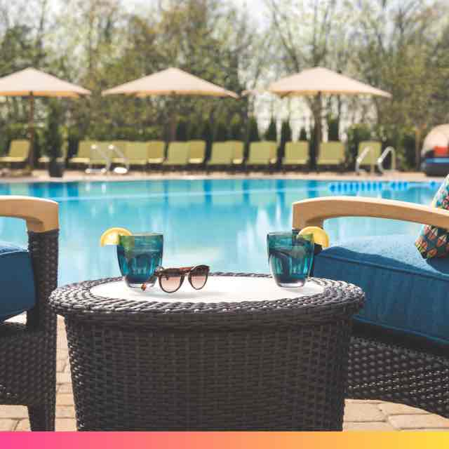 Two drink glasses and a pair of sunglasses sit on a table between two cushioned lounge chairs beside an outdoor pool