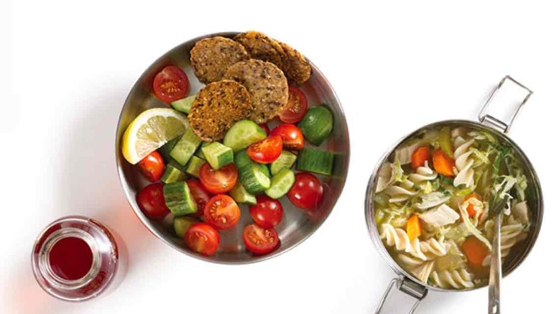Aerial view of a small metal bowl full of chicken noodle soup next to a larger bowl of chopped cherry tomatoes and cucumbers