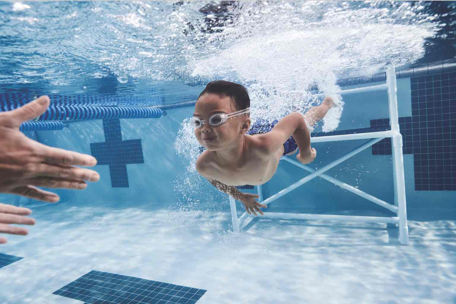 A child wearing swim goggles swimming underwater toward the outstretched hands of an adult in an indoor pool