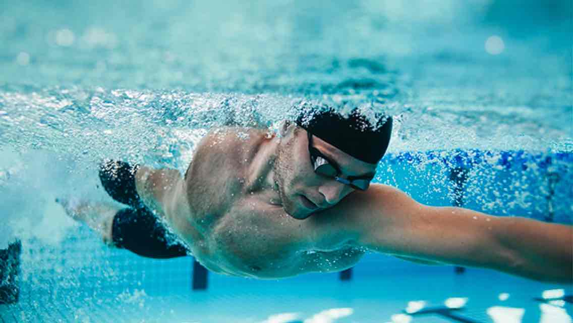 A man wearing a black swim cap and swim goggles glides through the water of an indoor pool at Life Time