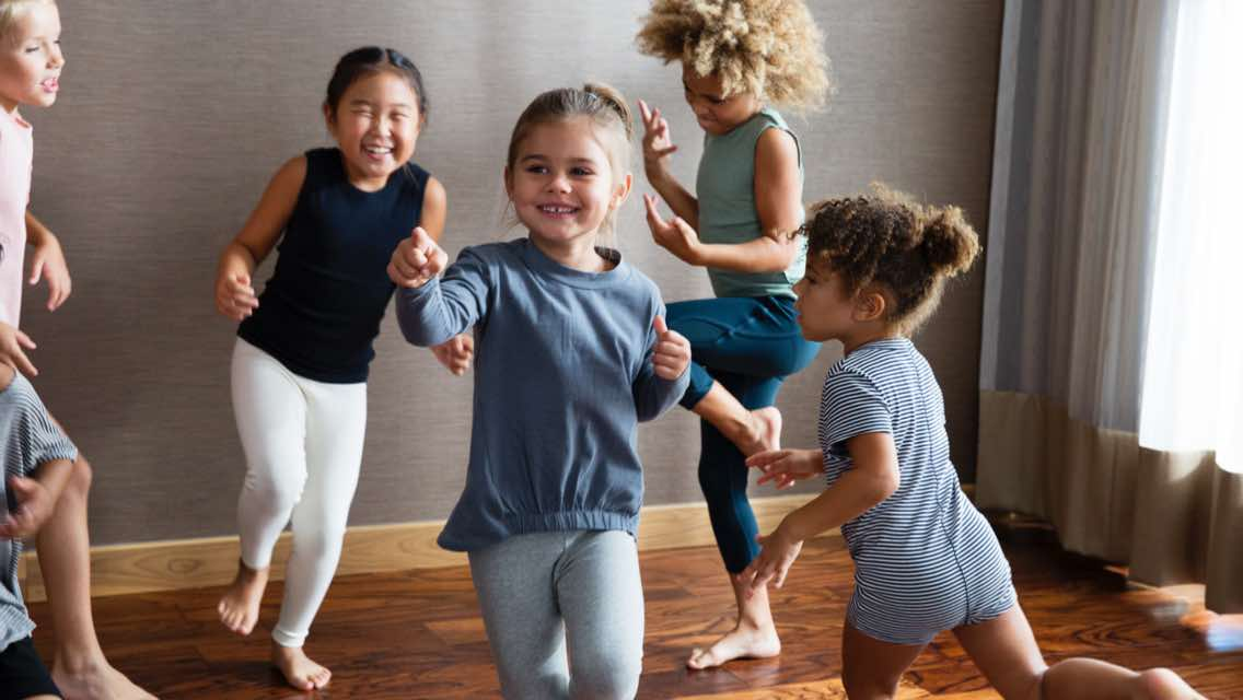 Five children dancing together in a brightly lit yoga studio