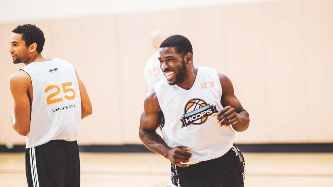 Two basketball players smiling while jogging down a basketball court
