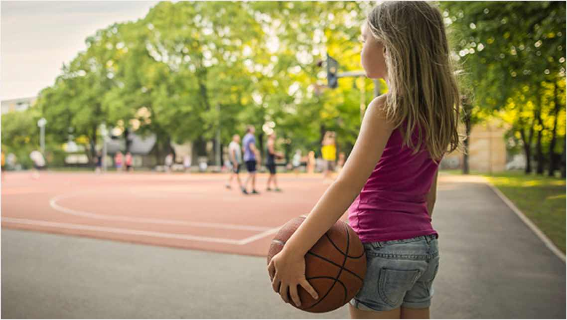 A female child holding a basketball while watching people play on an outdoor basketball court