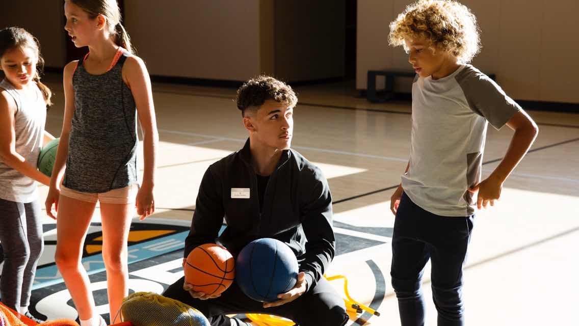 A Life Time coach sits on the ground holding two basketballs while three kids stand around him on an indoor basketball court