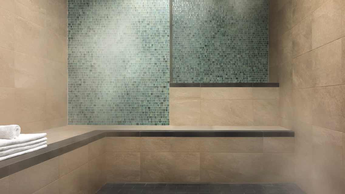 A luxurious steam room with tile walls and a stack of white towels