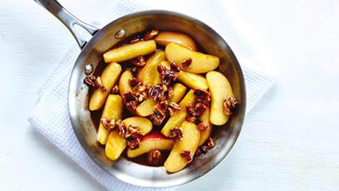 A bowl of sautéed apples topped with glazed pecans