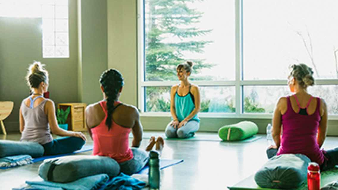 Four women wearing athletic clothing sit on yoga mats in a sunlit yoga studio