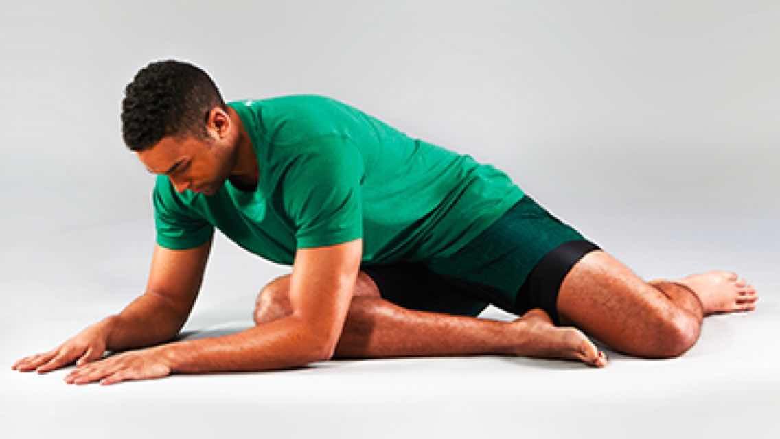 A man wearing green shorts and a T-shirt stretching in a yoga pose