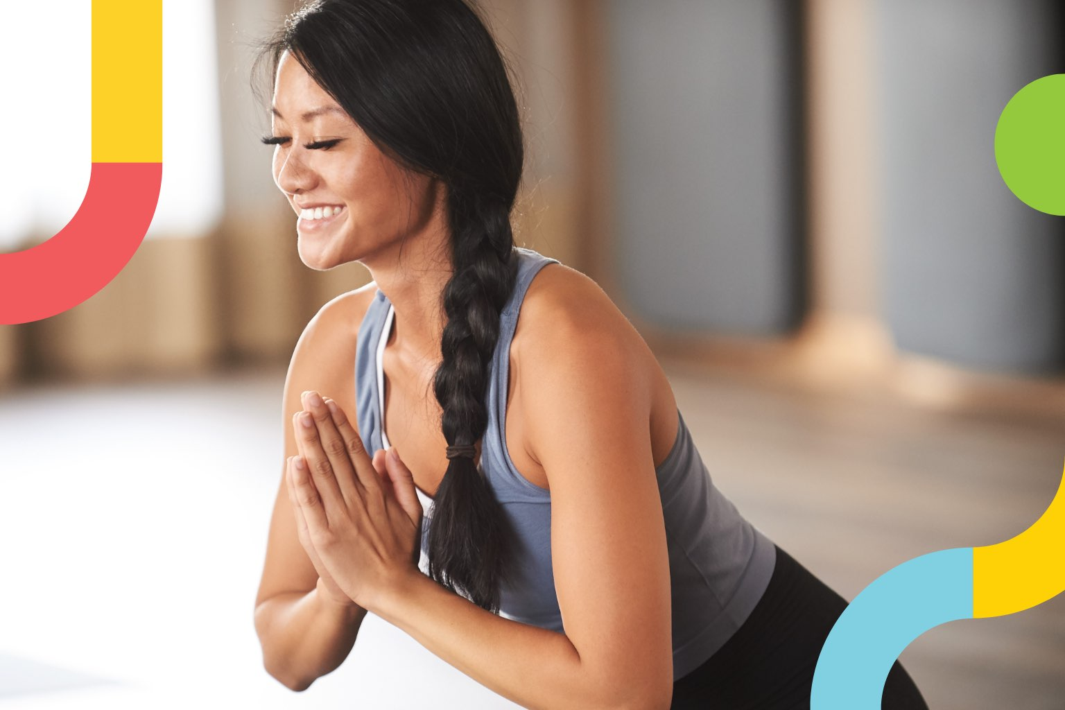 smiling woman with eyes closed and hands in prayer pose