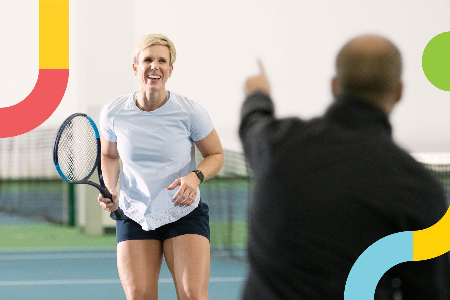 Woman holding tennis racquet smiling while man instructs her