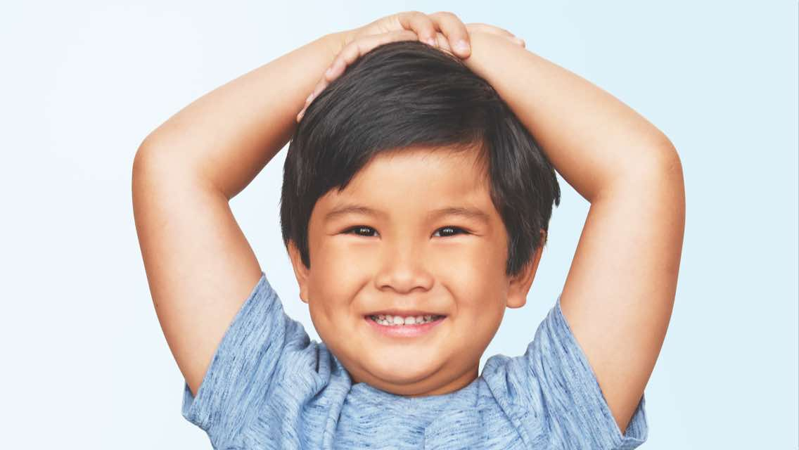 Male child holding his hands on top of his head