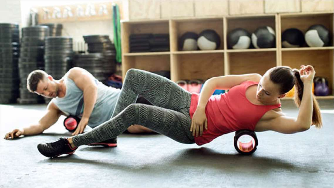Man and woman using massage rollers to recover from a workout