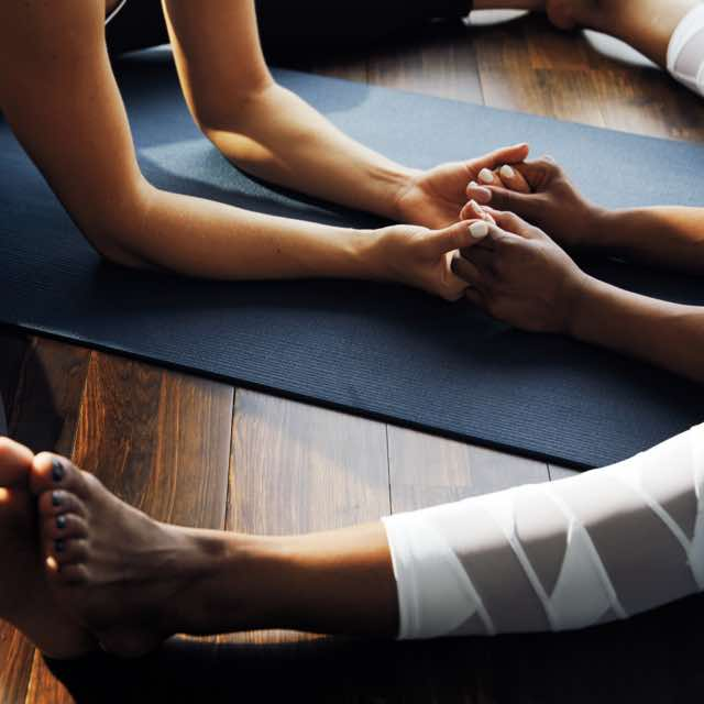Close view of two people holding hands on a yoga mat