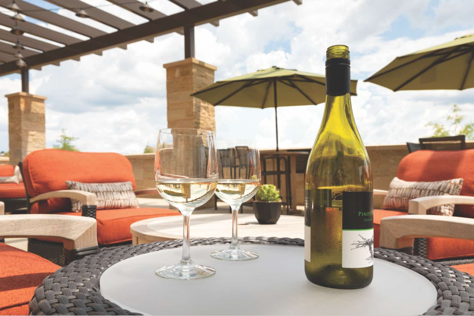 Two wine glasses and a bottle of wine on a table on an outdoor terrace