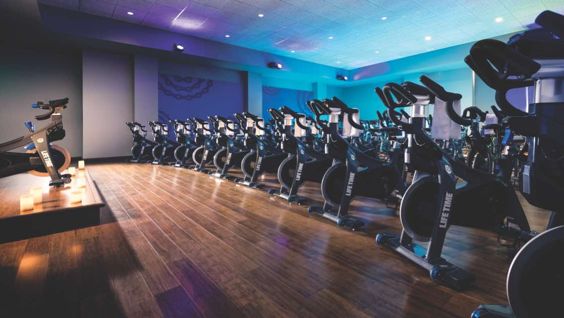 Dimly lit cycle studio with rows of indoor bikes at Life Time