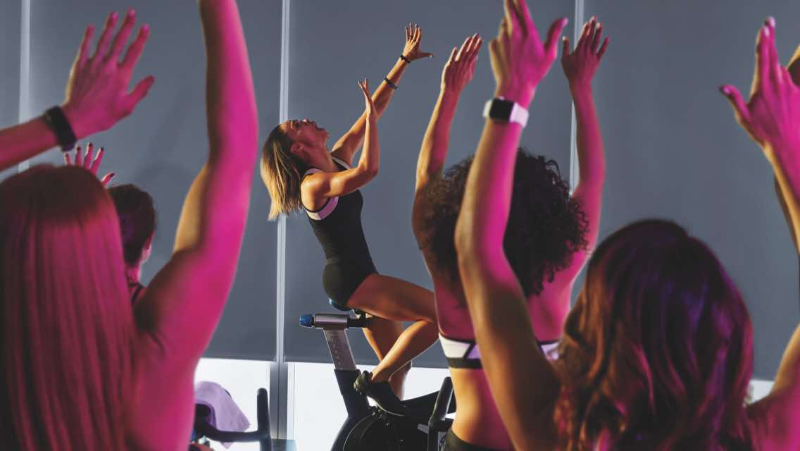 People with their hands in the air while participating in an indoor cycle class