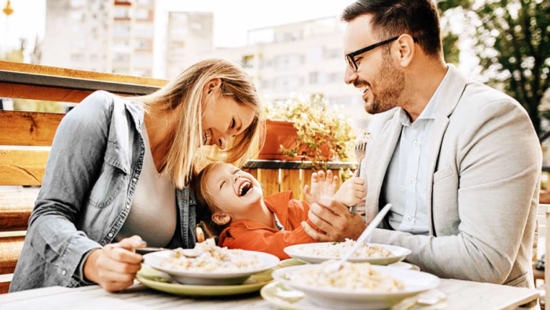 Two parents and a small child laughing together at a table over a meal