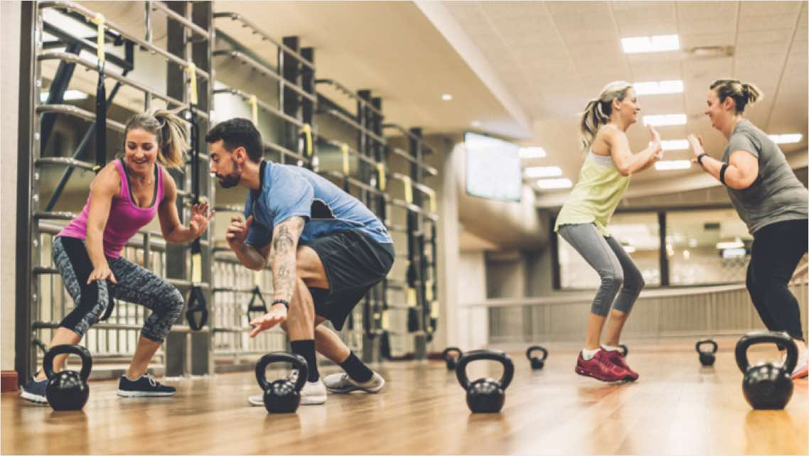 Four people working out with kettlebells on the fitness floor at Life Time