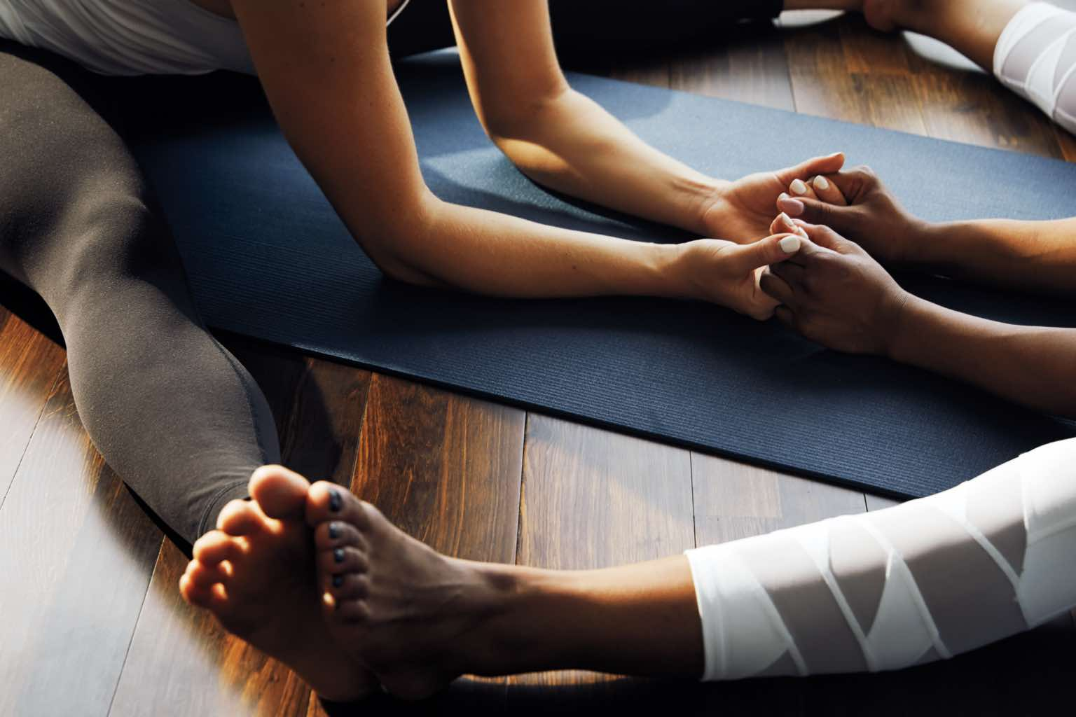 Two women holding hands and stretching on a yoga mat