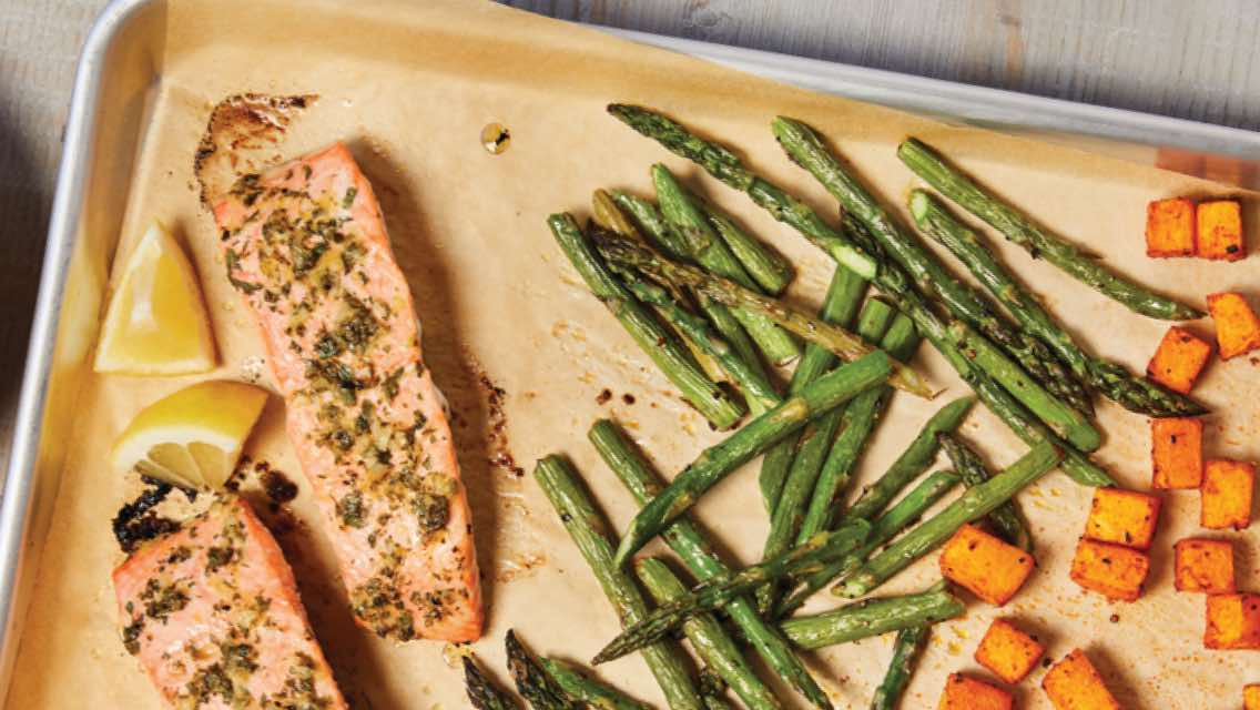 Sheet pan with baked salmon, asparagus and cubed pieces of butternut squash