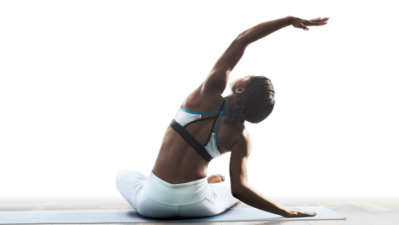 a women does a side stretch while sitting on a yoga mat
