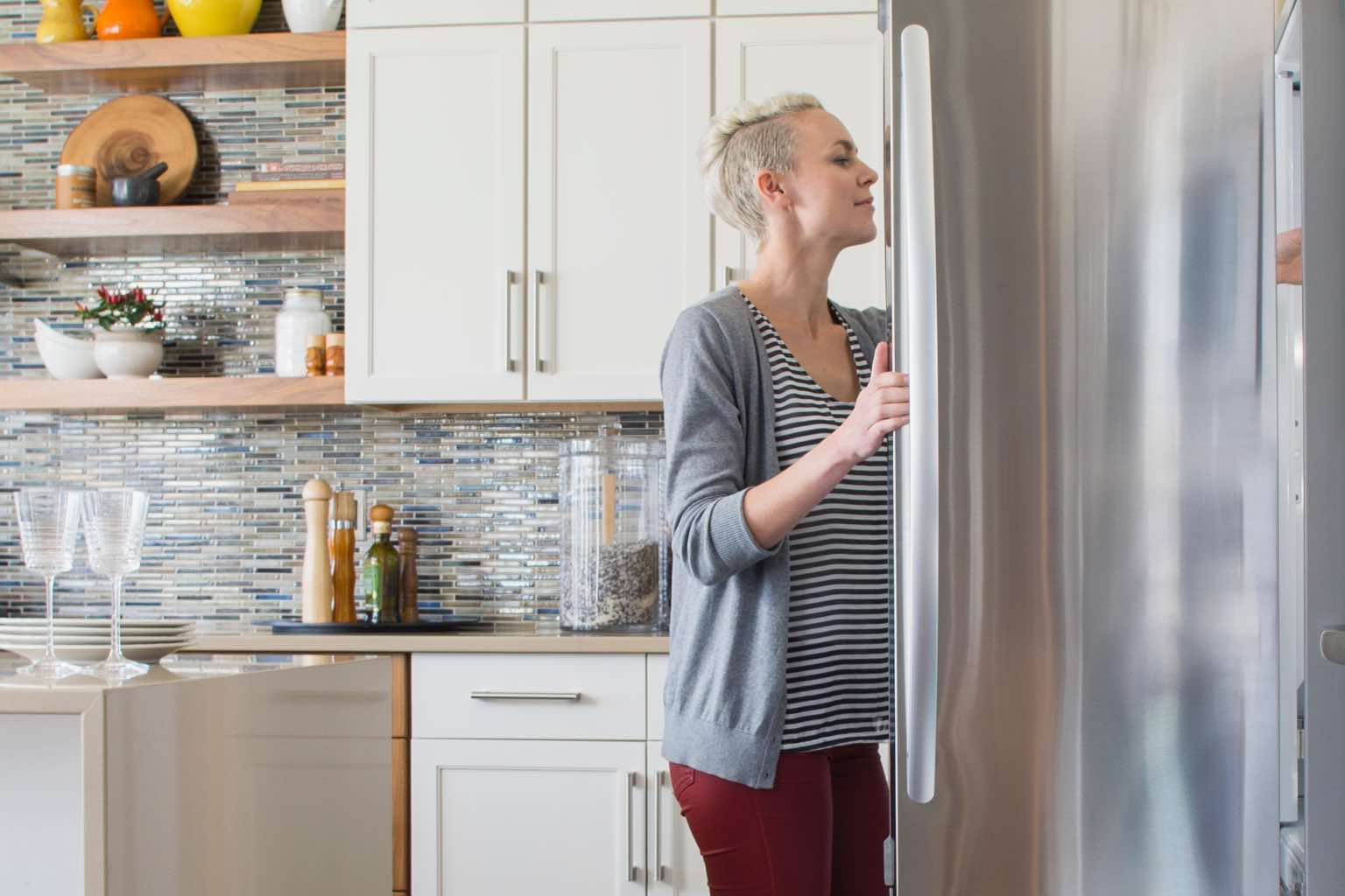 Woman reaching into her refrigerator while working from home.
